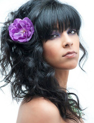 A smooth front set of bangs combined with loose curls brings attitude and adds flavor to this style.